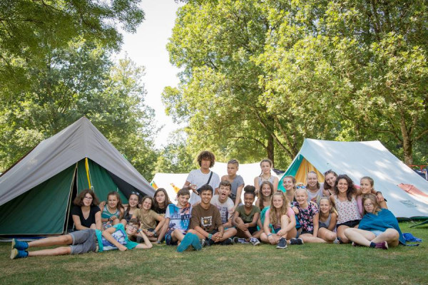 23 Kinder und Jugendliche sitzen vor ihren Zelten und haben alle ein breites Grinsen im Gesicht. Mit dabei ist auch Marsali.