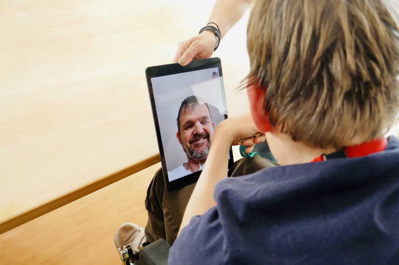 Ein Junge chattet mit seinem Vater über ein iPad.