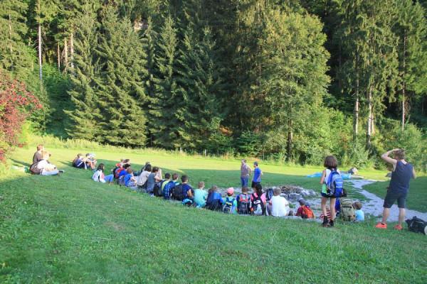 Rund zwei Dutzend Kinder und Jugendliche Sitzen am Waldrand im Kreis und werden von einem Detektiven fürs Schatzsuchen instruiert.