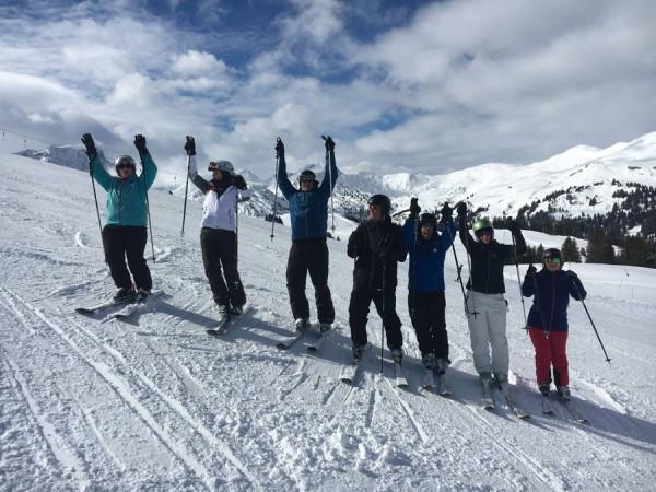 Sieben Skifahrende der SILEA-Stiftung stehen am Hang und heben Ihre Skistöcke in die Höhe.