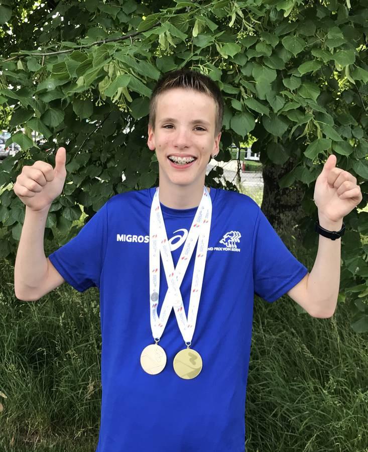 Fabian posiert mit seinen Medaillen, einer goldenen und einer silbernen.