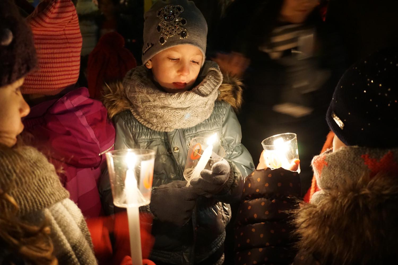 Drei Kinder in Winterkleidern und warmen Kappen halten Kerzen mit dem Friedenslicht in den Händen.